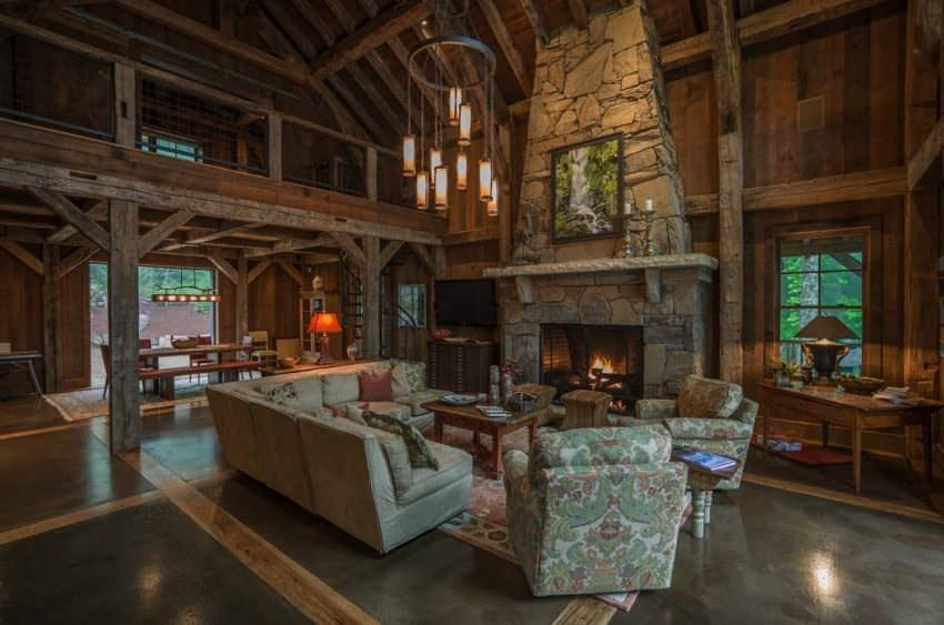 The great room is the show-stopper in this rustic house.  It's a large two-story room with towering stone fireplace, concrete floors with wood beams (very cool) that looks up to a second story landing.  What a fabulous room and house, all from an old barn.  Designed by RTM Architects