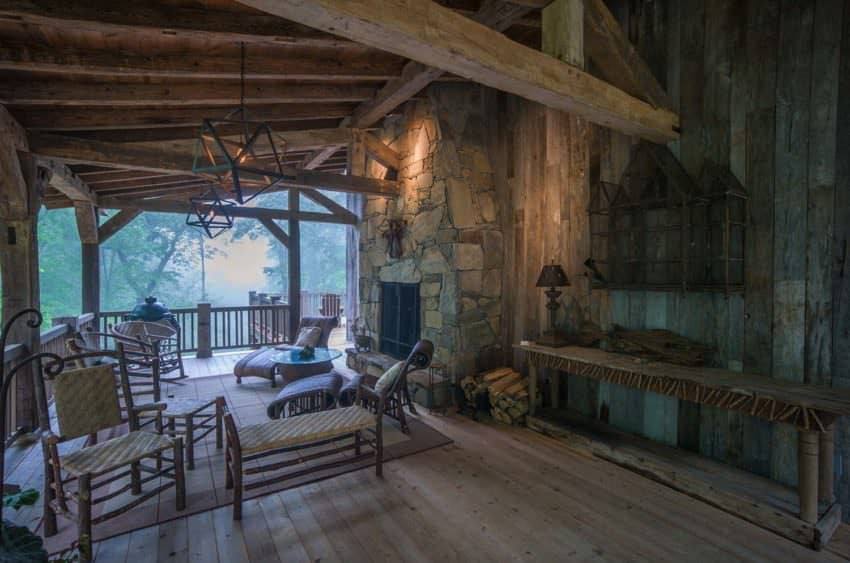 Is it 1875? It could be looking at this covered deck with stone fireplace, aged wood beams and matching patio furniture. Designed by RTM Architects