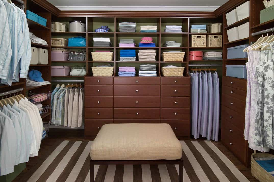 Here's an example of a custom-built walk-in closet with sitting ottoman and a built-in dresser along with plenty of space for hanging clothing and plenty of shelves.