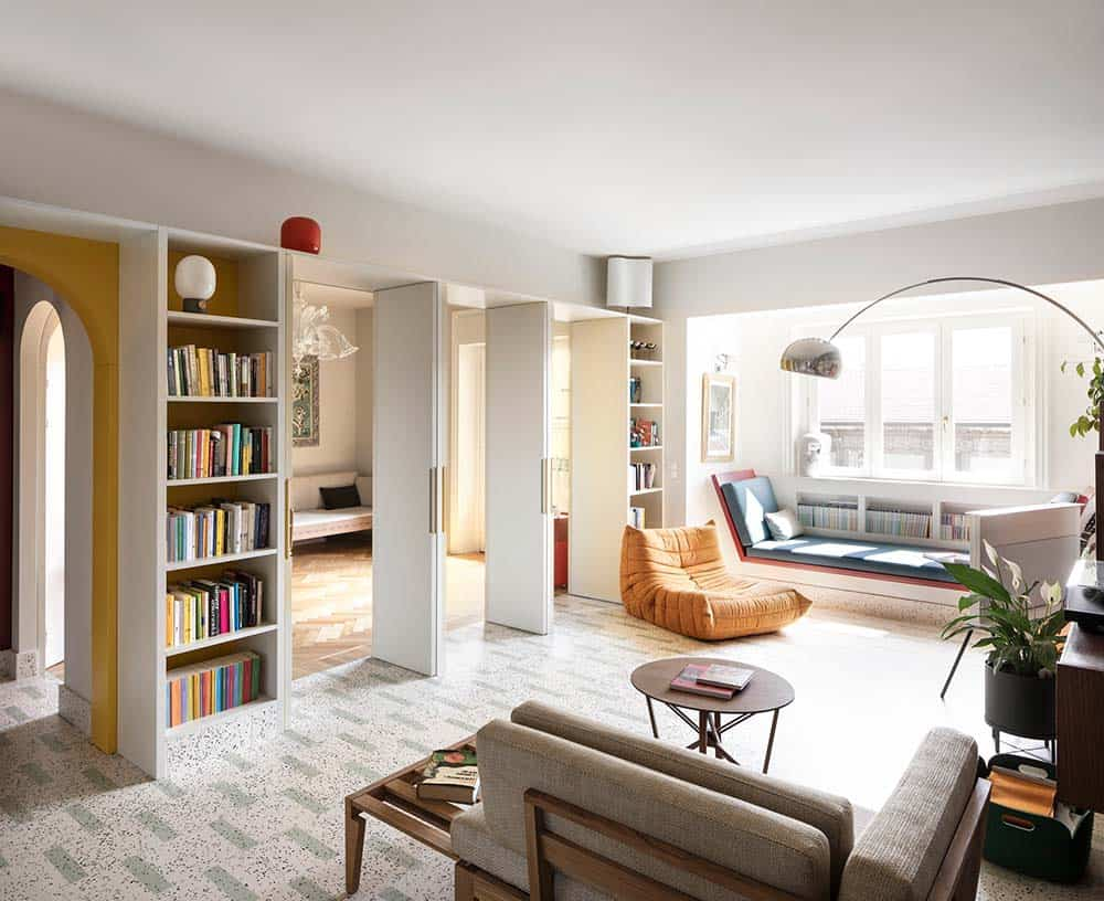 This is a bright interior of the apartment showcasing multiple built-in bookshelves and an abundance of natural lighting that brightens the reading nook with a built-in bench on the far side by the window. This was designed by ATOMAA.