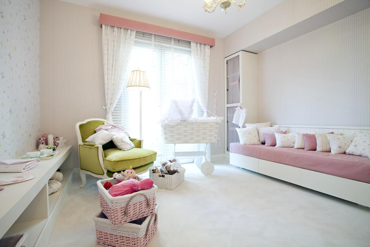 White nursery room with a long bench seating and a carpet flooring. The pink details of the room looks perfect with the white surrounding.