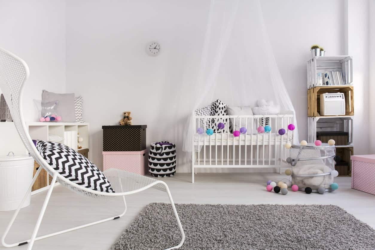 This white nursery room offers a stylish blend of black and white shades. The gray rug also fits well with the room's style.