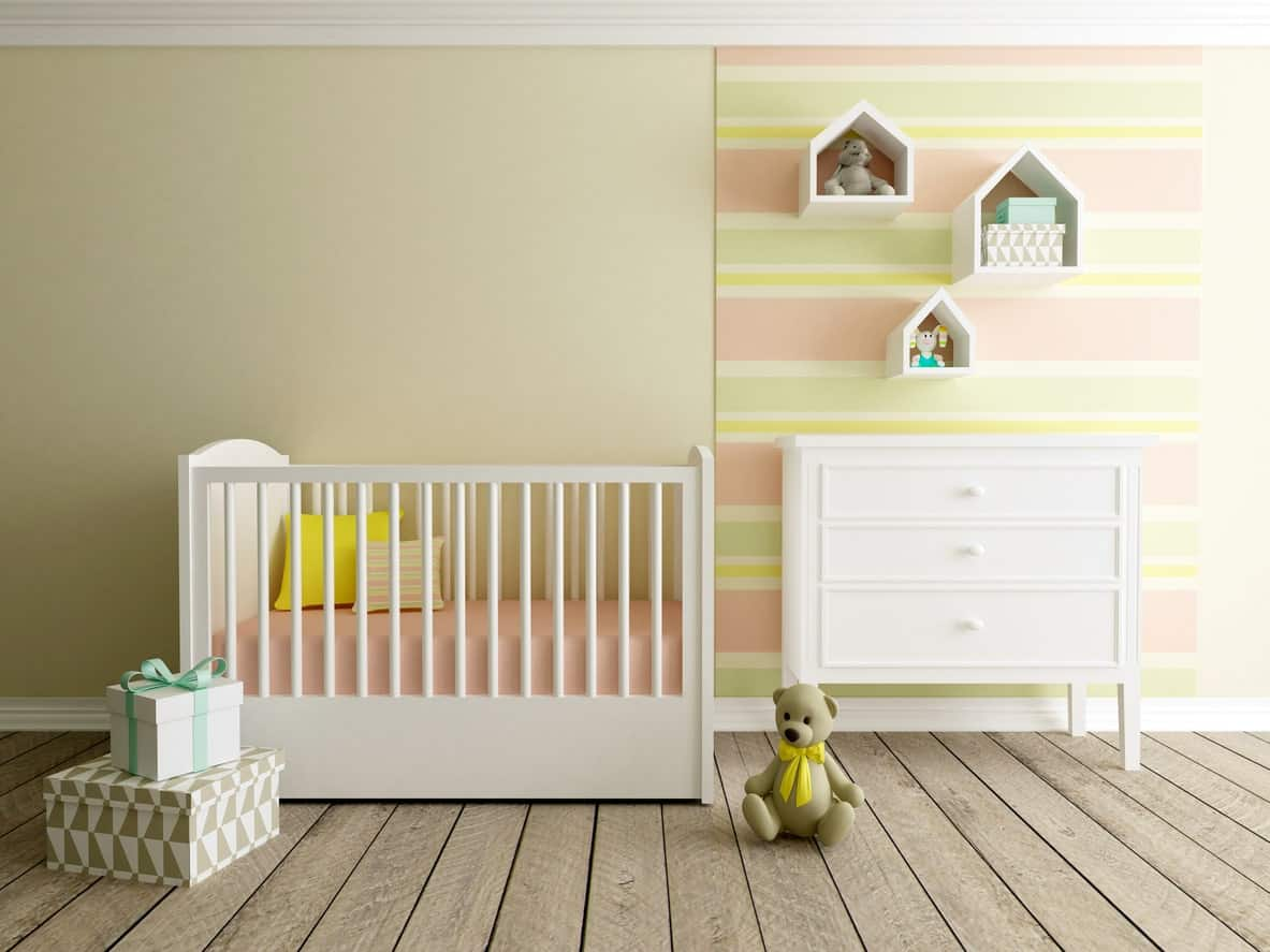 This nursery room offers a peaceful vibe with its walls. The hardwood flooring fits well while the white furniture add brightness to the room.