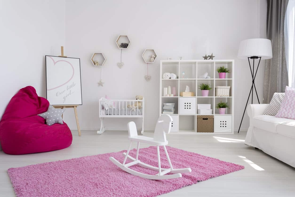 White nursery room with a shade of pink. The gray curtains looks beautiful while the red chair surely attracts attention.