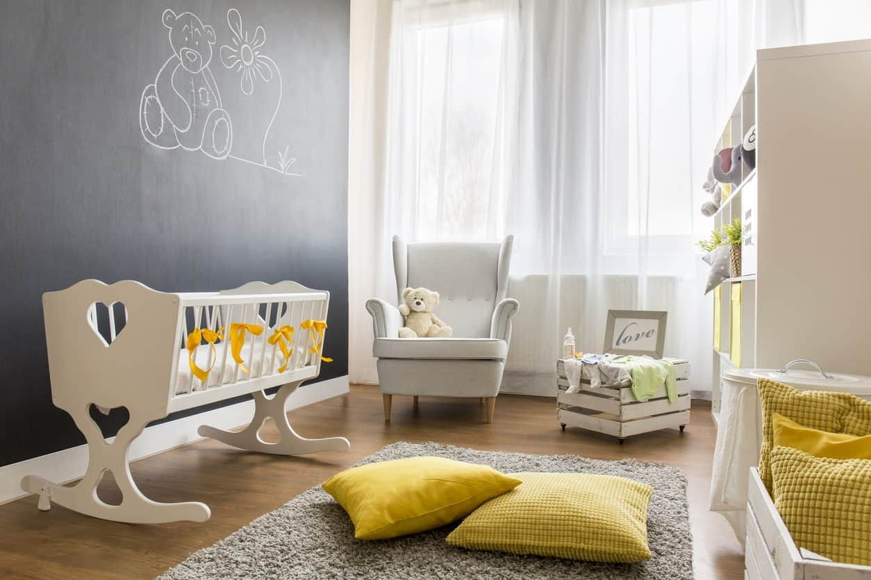 Small nursery room with black and white walls. The yellow shade looks great with the white curtains, while the vinyl flooring topped by a gray rug looks like a perfect pair.