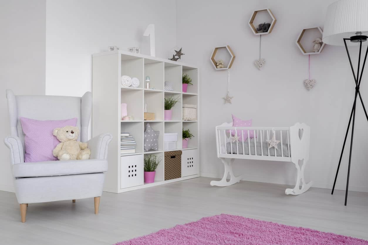 This white nursery room with pink shade looks absolutely stunning. The shelves are perfect together with the wall decors.