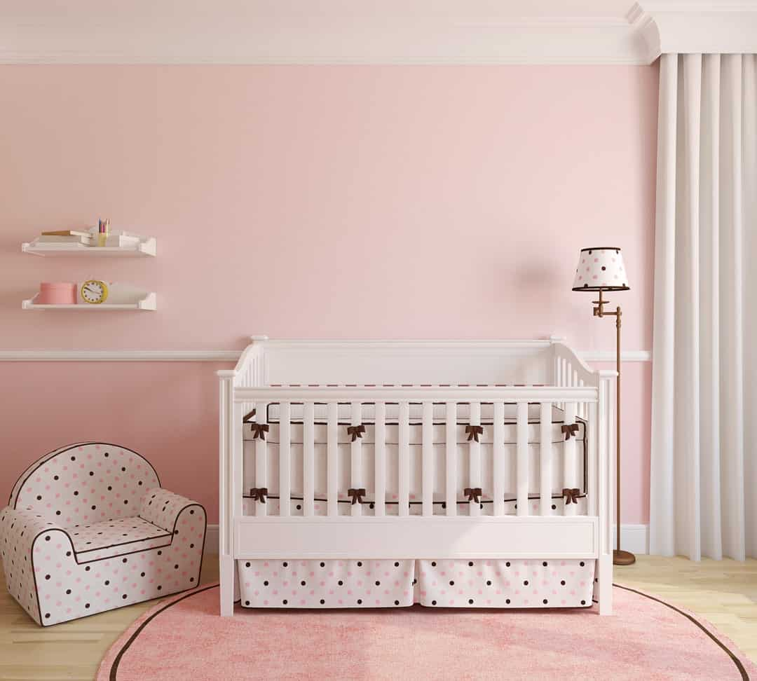 Pink nursery room for baby girl featuring a stylish crib, baby club chair and round pink rug. The floor lamp matches with the crib and chair.