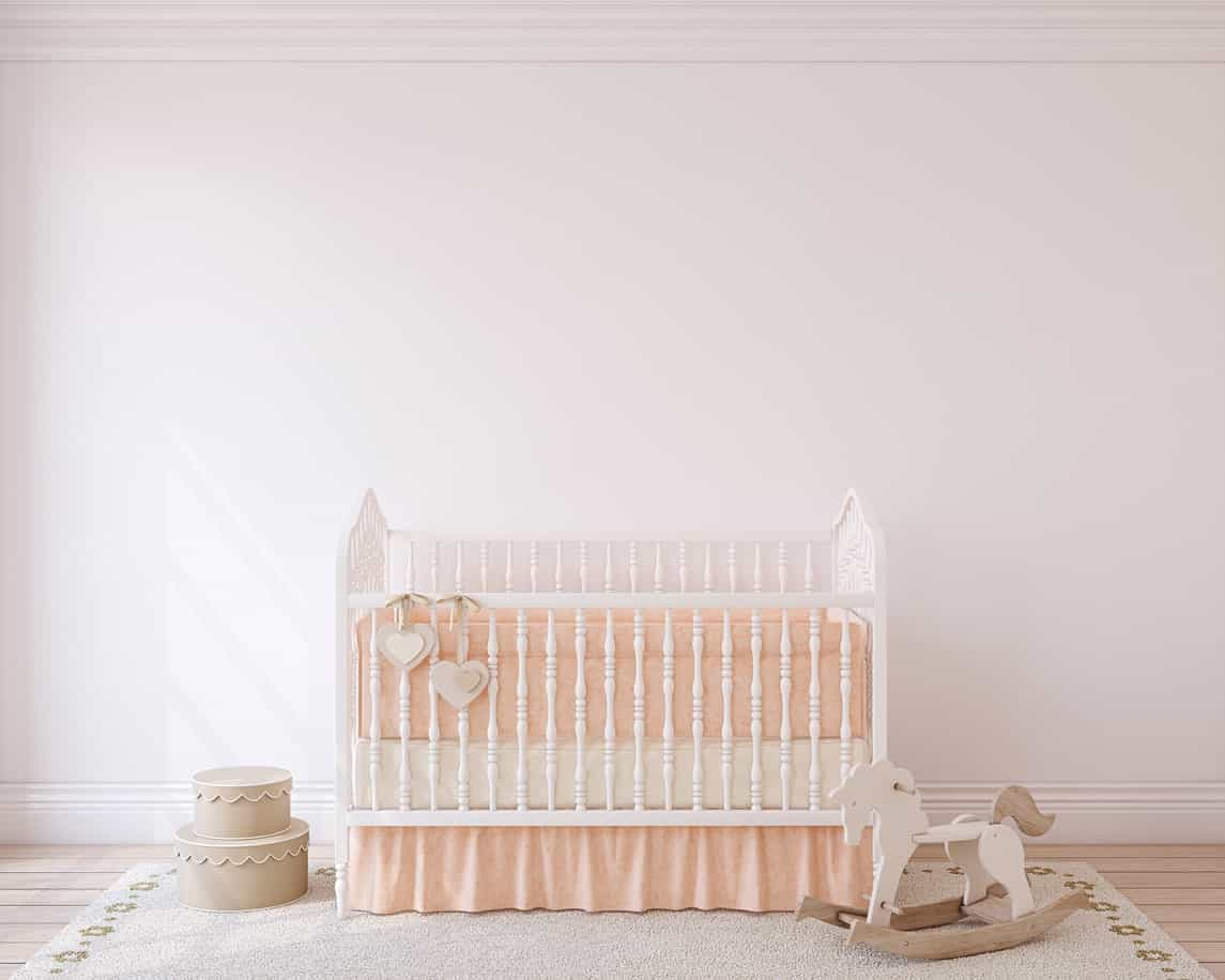 Minimalist baby girl nursery room featuring a bright colored crib with white walls and rug set on a hardwood flooring.