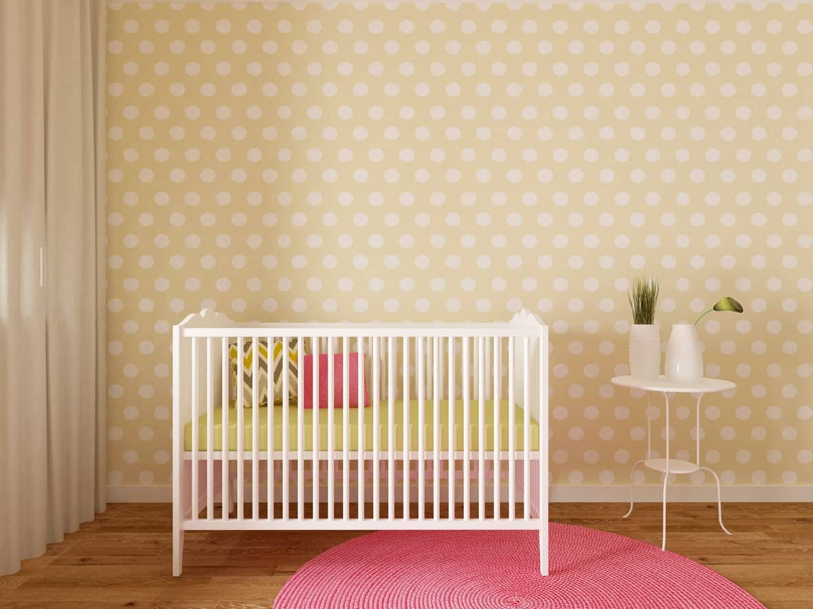 This yellow nursery room with details of white and hardwood flooring topped by a red round rug looks great for a baby girl.