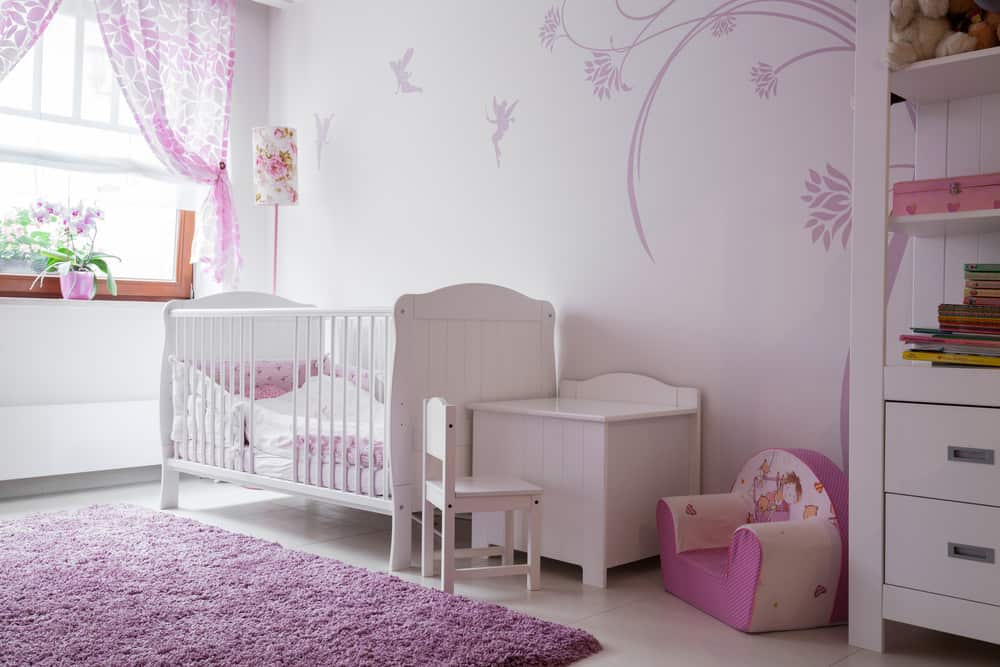 Fuchsia and white baby room.  The plush purple floor rug is a great addition if you have hard flooring because it's a soft place to let your infant roll/crawl.