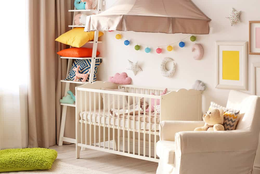 Baby Girl Nursery Decor Playful baby girl room with ladder shelf and fun wall art. Armchair  situated next to