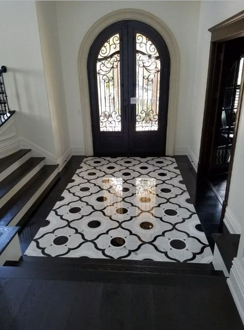 A classy foyer featuring an glamorous flooring with black paint and white walls. The simple combination of the colors are just absolutely beautiful.