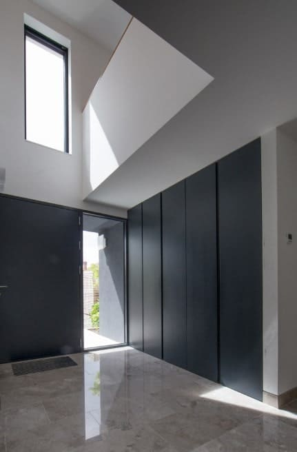 A simple foyer featuring a simple combination of black walls and white ceiling. The tiles flooring blends well to the hallway's style as well.
