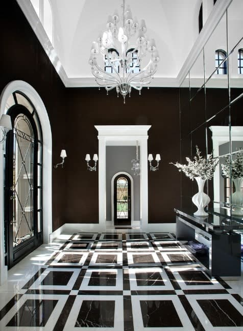 Glamorous foyer filled with elegance. The flooring and the dark colored walls fits perfectly together. The white details, along with the grand chandelier showers the hall with class.