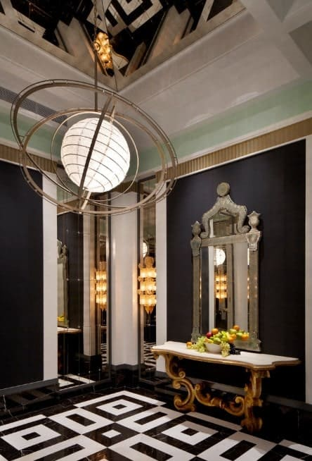 This elegant black foyer features a classy flooring and ceiling light. The other details of the hall look so glamorous.