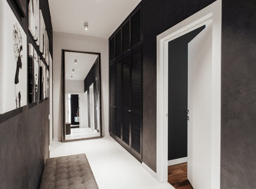 A foyer with a combination of white, gray and black colors. There are several wall decors giving life to the hallway.