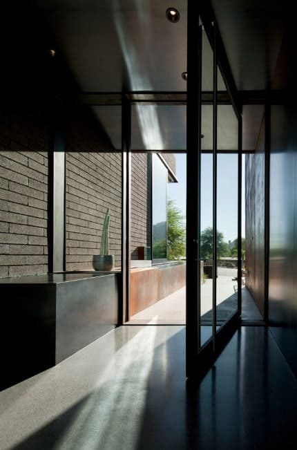 This dark foyer with black and gray walls features a glass doorway letting the sunlight through, brightening the space.