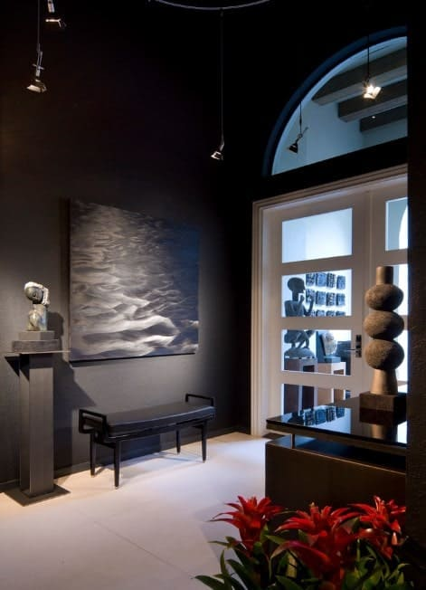 Dark colored foyer featuring a black wall with a stylish decor. The white door and flooring blends well with the hall's style.