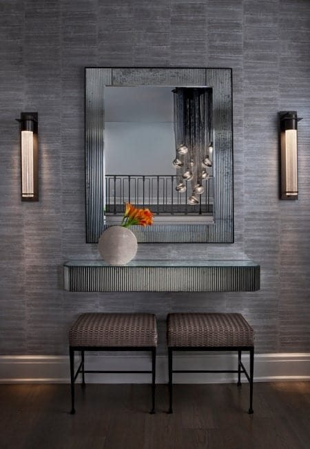 This foyer features a hardwood flooring, stylish gray walls with wall lighting installed.