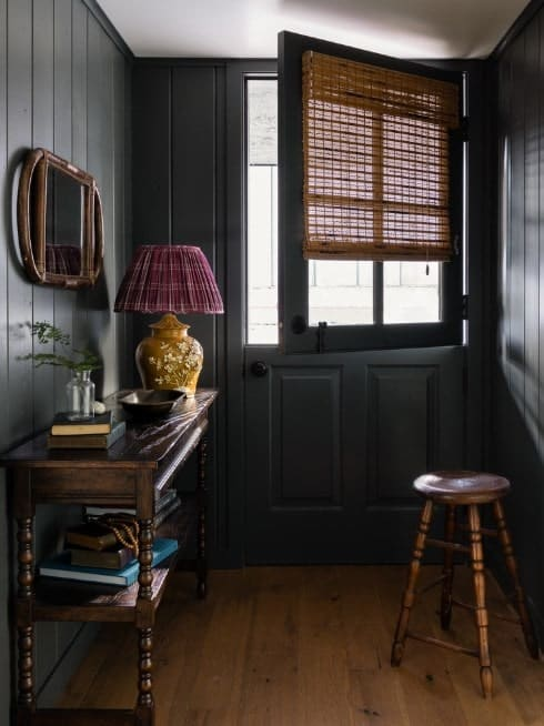 This small foyer features a combination of gray and black walls. The hardwood flooring and other details blend well with the foyer's style.