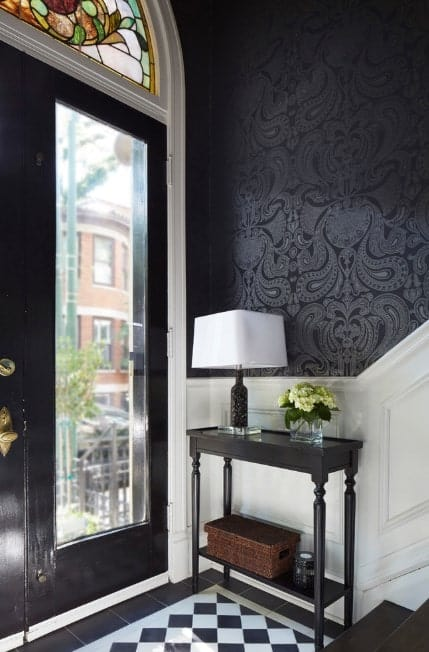 This small yet classy foyer features a stylish tiles flooring, a combination of white and stylish black walls and a dark hardwood staircase.