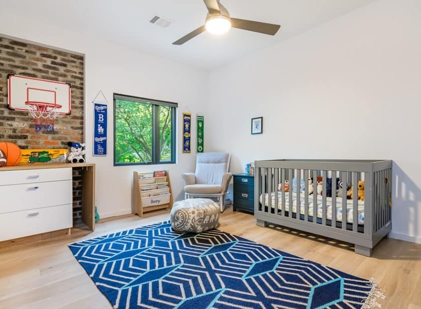 This room is great for longer term usage as your baby. The room transitions from a newborn crib area to a wider playing area complete with a basketball hoop to give your boy plenty of space to play in as he grows older. Designing a room with transition in mind is a great way to minimize costs of redecorating and let you simply swap out the crib for a bed later on without needing to change much.