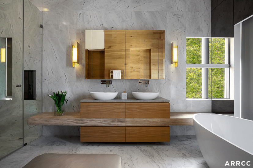 Fabulous modern primary bathroom with gray wall and custom counter with two white vessel basins - designed by ARRCC.