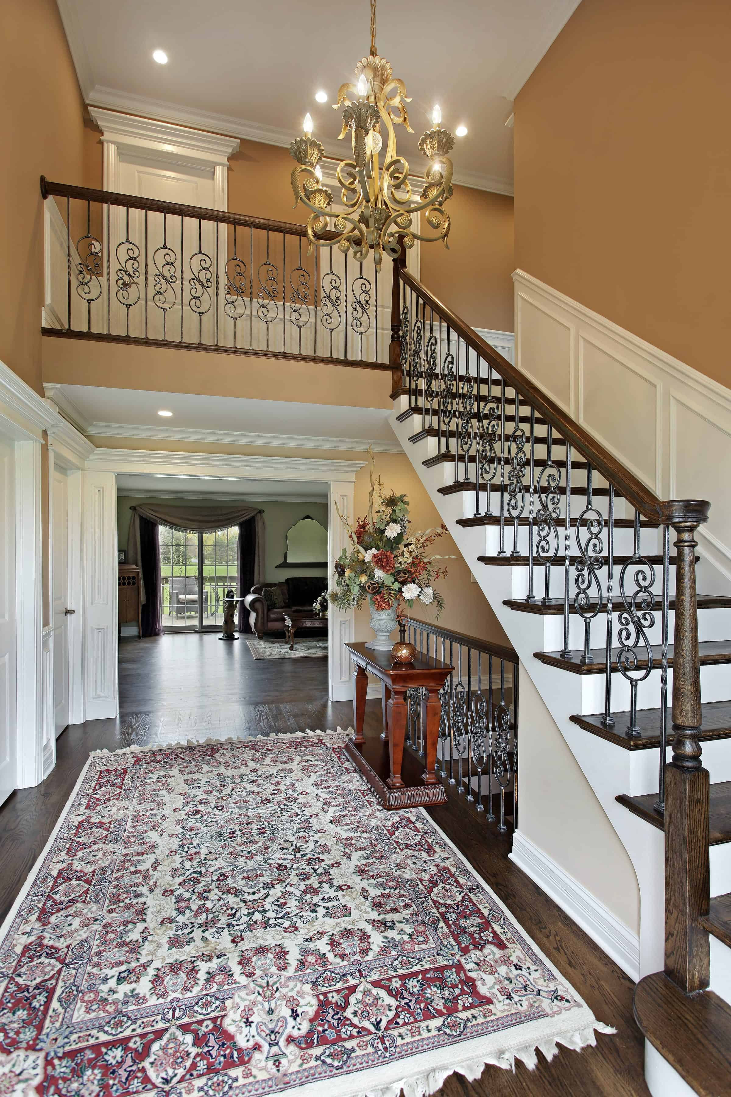 This foyer features a hardwood flooring topped by a stylish rug. The staircase looks beautiful lighted by an elegant chandelier.