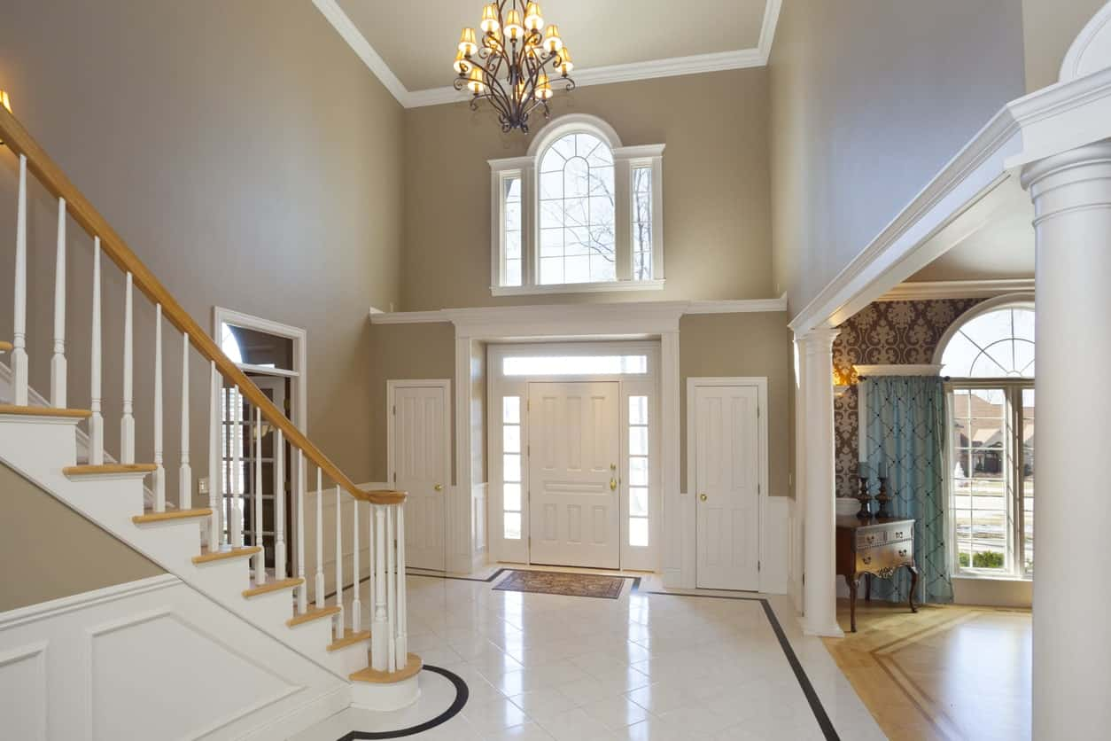 This classy white foyer features a tiles flooring and a beautiful staircase lighted by an elegant chandelier.
