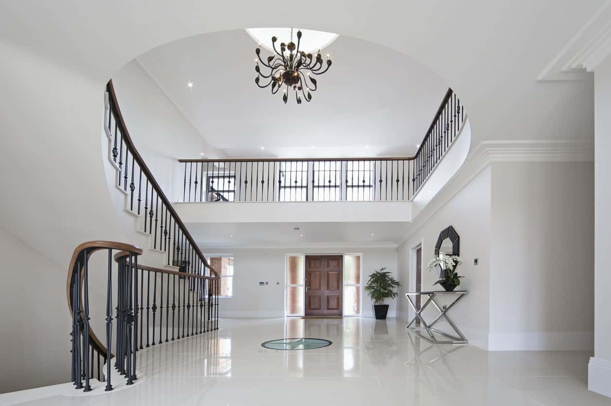 This large foyer is surrounded by white all over the place. The flooring mirrors the gorgeous chandelier lighting set on a high ceiling.