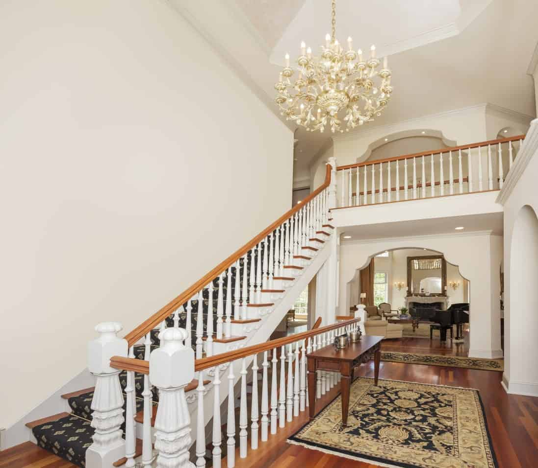 Classic foyer boasting a smooth hardwood flooring, white walls and white staircase railings. The rugs are so charming as well as the elegant chandelier.