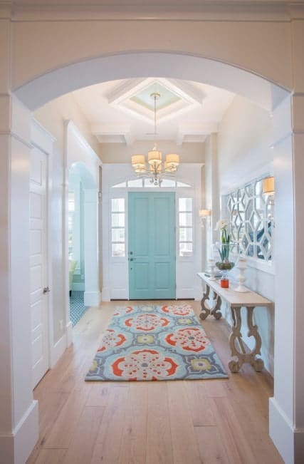 Bright foyer boasting a white and green color combination along with a colorful rug set on a hardwood flooring. The hallway is lighted by a beautiful chandelier.