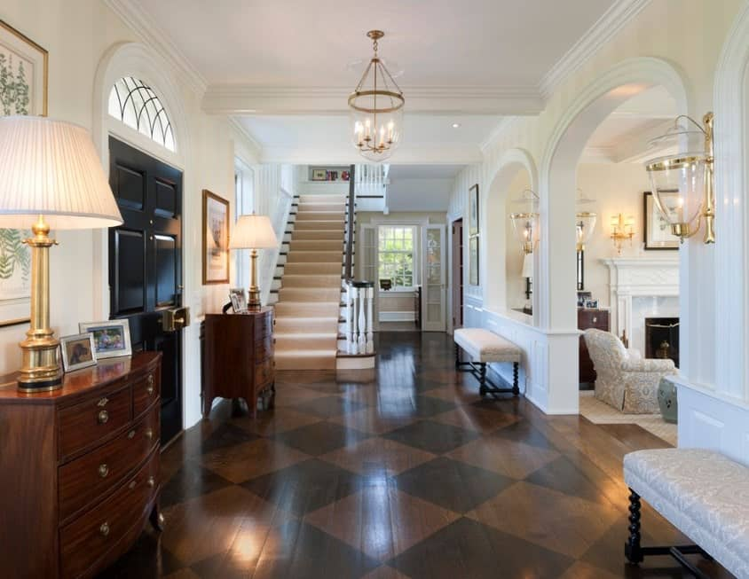This large foyer features a stylish hardwood flooring with a checker pattern. The white walls looks perfect with the foyer's style. The chandelier looks great as well.