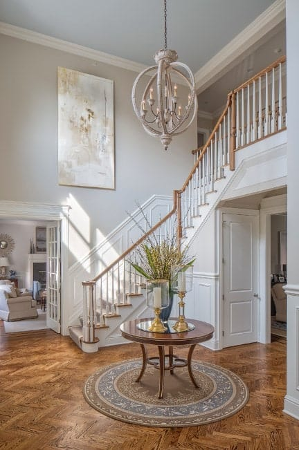 This foyer features a beautiful flooring, white walls with a stylish wall decor and a gorgeous chandelier brightening up the space.