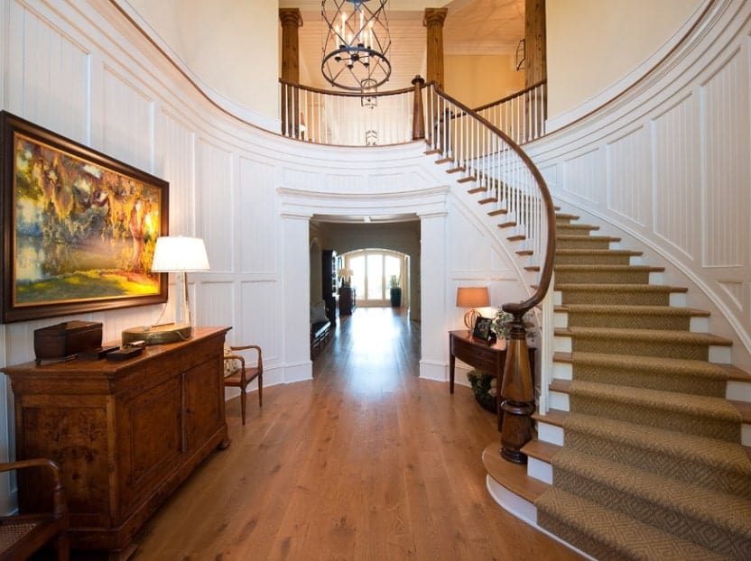 Large foyer with white walls and hardwood flooring lighted by a small chandelier. The staircase looks gorgeous too.