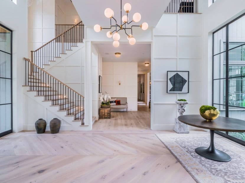 Bright large foyer featuring a hardwood flooring, white walls and glass doors and windows overlooking the outdoor space. The hall is being lighted by a classy chandelier.