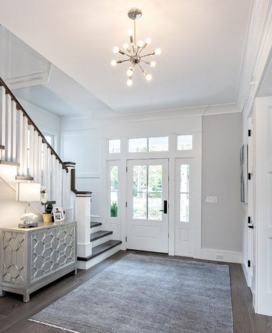 This bright foyer features white walls, dark hardwood flooring topped by a gray rug and a charming small chandelier.