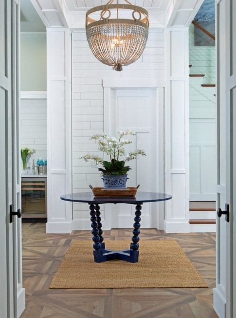 This foyer features a stylish flooring topped by a rug and a center table. Just above it is a elegant-looking chandelier.