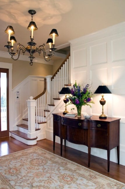 This foyer boasts a very charming chandelier lighting up the beautiful hall featuring a vinyl flooring topped by a classy rug.