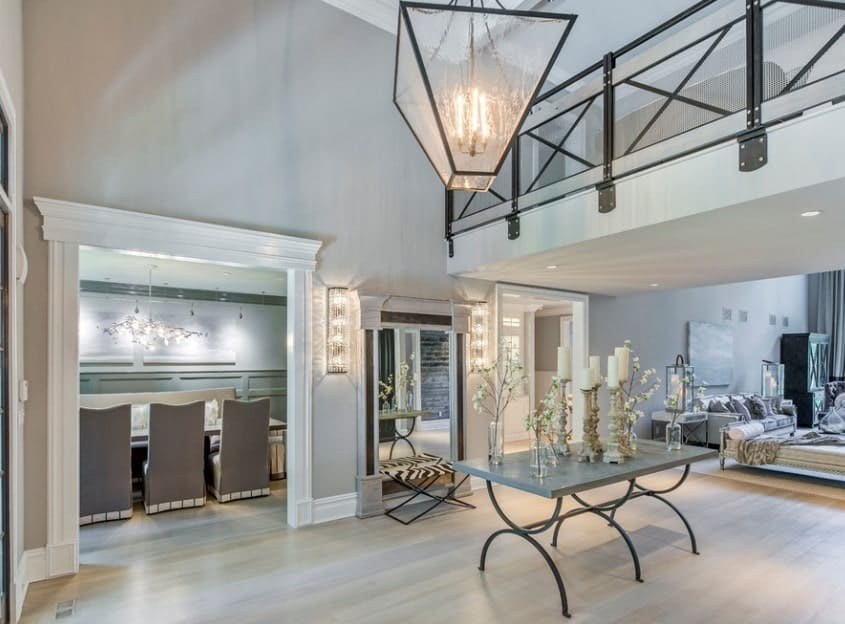 This foyer features light gray walls and hardwood flooring. It also offers a beautiful center table topped by indoor plants and candles. Just above that is the charming chandelier.