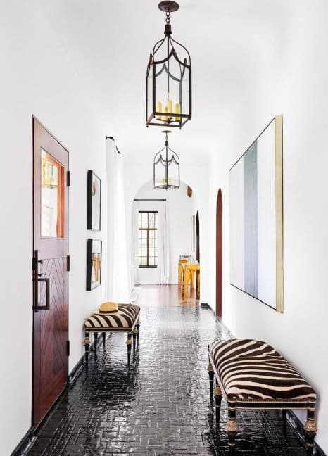 This foyer boasts white walls and dark tiles flooring. The seats and wall decors are absolutely perfect together while the small chandeliers add brightness to the space.