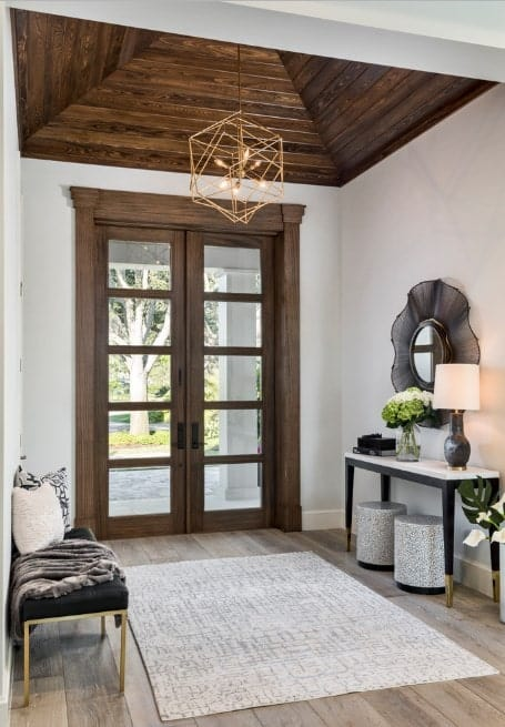Small foyer featuring a hardwood flooring topped by a rug, white walls and brown ceiling. The foyer offers a beautiful small chandelier as the lighting.