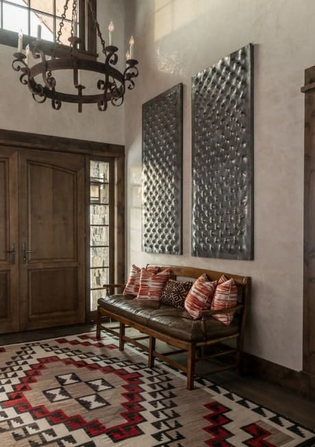Classy foyer with a hardwood flooring topped by a charming rug. The wall and the decors are perfect together while the chandelier adds elegance to the place.