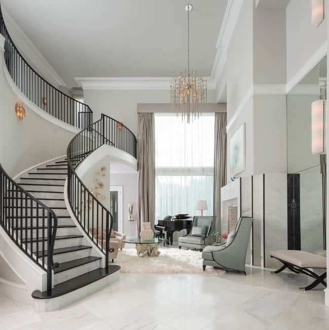 This large foyer boasts a white marble tiles flooring and light gray walls. The staircase looks perfect with the home's style while the chandelier matches the elegant lighting all over the place.