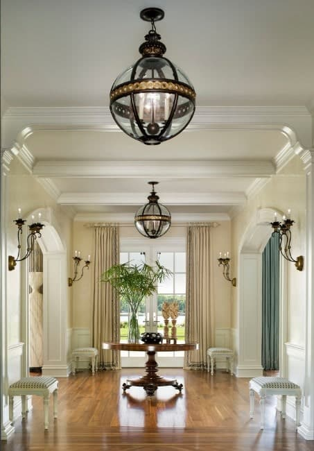This gorgeous foyer offers a shiny flooring, beautiful white walls and ceiling along with a charming set of wall lights and chandeliers.