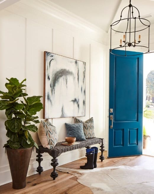 This foyer looks lovely with its blue door, wall decor and flooring rug. The chandelier looks perfect too.