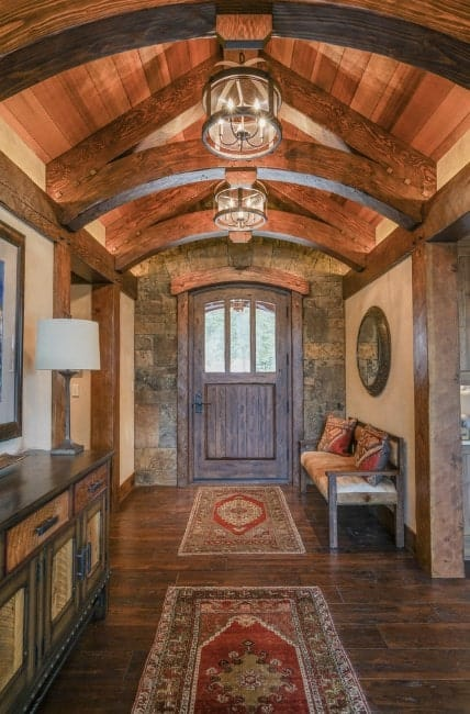 This rustic foyer featuring a classy rug and archway ceiling is just magnificent. This foyer is also lighted by a couple of small chandelier.