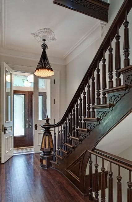 This foyer features white walls and brown flooring and staircase. The chandelier is the perfect fit for the foyer's style.