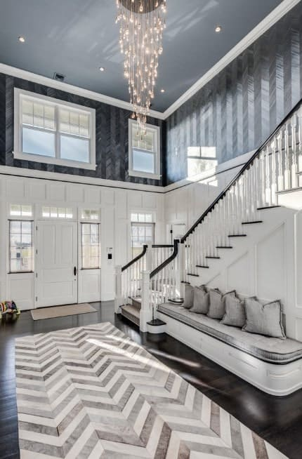 This foyer offers a white and dark color combination. The hardwood flooring topped by a rug, white and black walls are just perfect with each other. The hall is lighted by a charming chandelier.