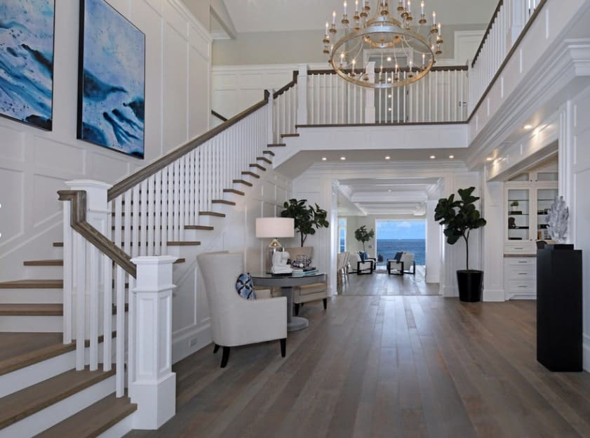 This white foyer features a set of blue stylish wall decors and a hardwood flooring. The hall is lighted by recessed lights and a large chandelier.